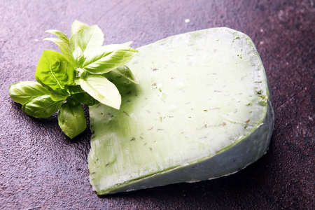 Green pesto cheese and basil leaves on rustic background