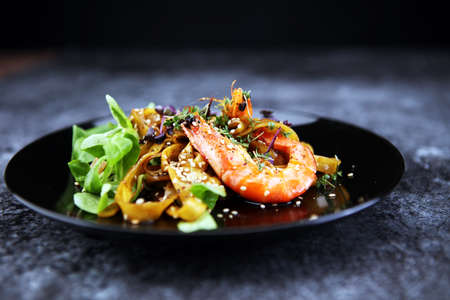 lunch dinner dish meal in a gourmet restaurant. food fish elegant gourmet plate. sea seafood shrimp on dark plate