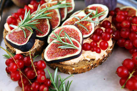 Healthy sweet figs fruit toast with cheese, honey and flower. Fresh fig fruit and flower decoration.