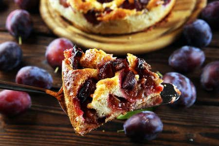 Rustic plum cake on wooden background with plums around. Plum pie concept Zdjęcie Seryjne