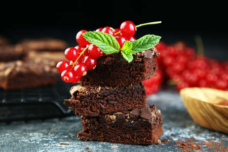 Brownie stack, chocolate cake on rustic wooden board on table