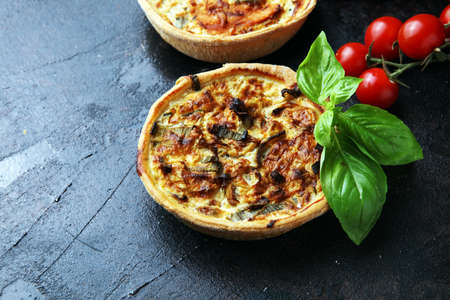 Savory mini quiches or tarts on a rustic board. Flaky dough pies. Fresh basil and tomatoes on handmade quiche Banque d'images