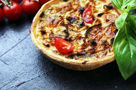 Savory mini quiches or tarts on a rustic board. Flaky dough pies. Fresh basil and tomatoes on handmade quiche Zdjęcie Seryjne