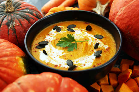 Roasted pumpkin and carrot soup with cream and pumpkin seeds and herbs on wooden background. Zdjęcie Seryjne