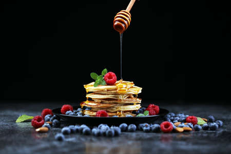 Homemade crepes served with fresh raspberries and powdered sugar on rustic table