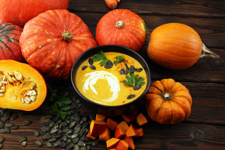 Roasted pumpkin and carrot soup with cream and pumpkin seeds and herbs on wooden background. Reklamní fotografie