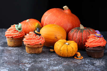 halloween cupcake and pumpkin on a dark background. sweets with cupcakes for the celebration