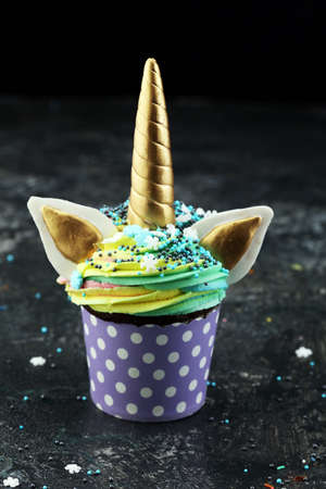 Unicorn cupcakes decorated with colorful buttercream icing and sprinkles on dark
