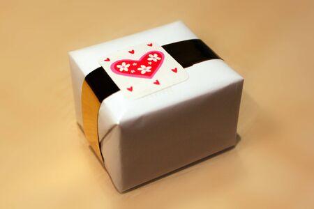 generoso: Contratación presente envuelta en blanco, papel de embalaje y etiqueta oro con corazón y flores rosas