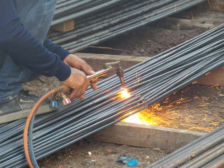 on rebar: A cutting torch to cut rebar Stock Photo