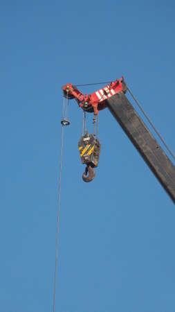poleas: Industrial colgante gancho en la cadena carrete y el cielo azul de fondo. Foto de archivo