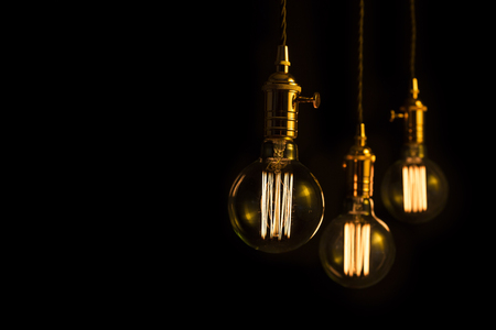 Three filament light bulbs with copy space.