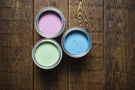Pastel paint tins on wooden floorboards.
