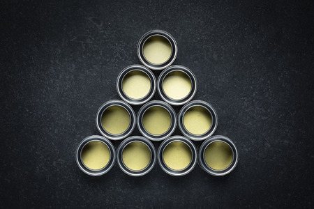 Arrangement of 10 empty open paint cans on black marble background.