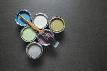 Pastel paint tins and brush on grey marble surface.