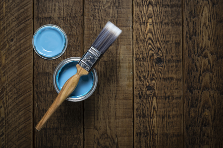 Can of pastel blue paint with brush on wooden floorboards.