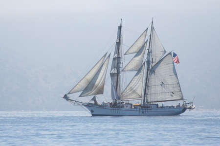 A tall ship ghosts along Catalina's shore line in hazy sunshine