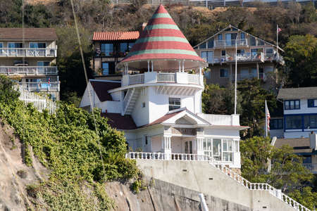 Brightly colorod Holly House in Avalon California, Catalina Island. The Lookout Cottage stands perched on a cliff overlooking Avalon Harbor surrounded by green and vacation cottages.