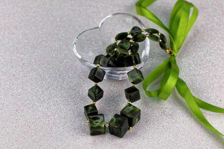 adn: collar de piedras verdes sobre fondo blanco. San Valentín del ADN de las madres día del tema