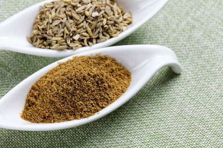 aromatic: Aromatic fennel powder and seeds on  texture background