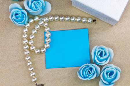 aniversary: Pearl necklace with blue satin background. Aniversary theme