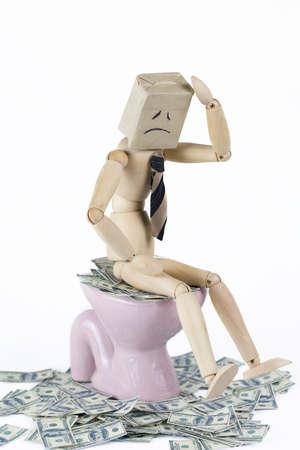 depress: wooden businessman depress sitting on toilet bowl filled with cash