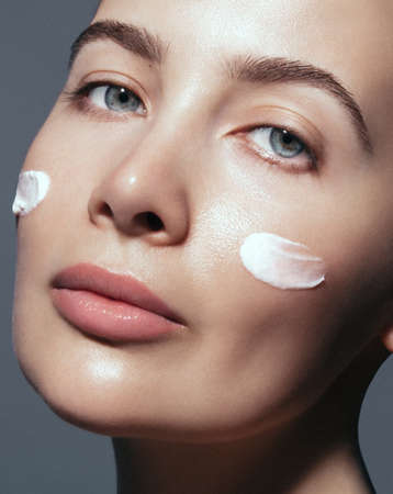 Dermatology, Rejuvenation, moisturizer and skin care. Close up portrait of beautiful model with cream in the face.Clean and fresh, lifting and body care product