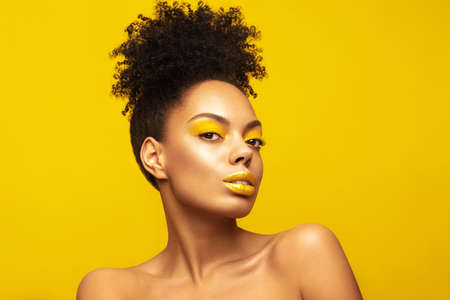Portrait of Young African American girl model with creative make up posing against yellow background Banque d'images