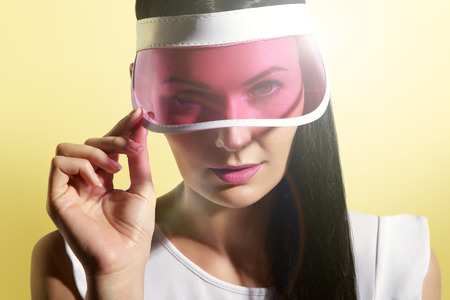 sex appeal: woman in a sun visor on a sunny yelow background Stock Photo
