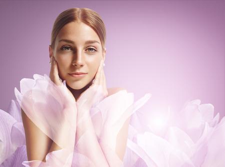schoonheid vrouw aan te raken haar gezicht. Vrouw tussen de bloemen