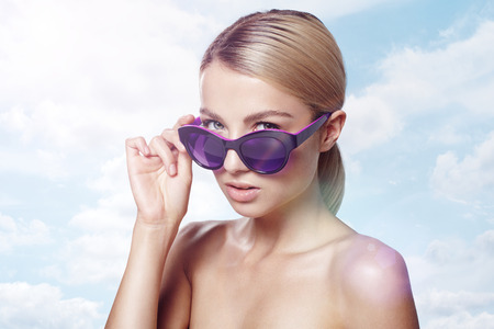 slender woman: pretty girl in sunglasses on a cloud background