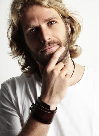 long hair man: blond man touching his beard Stock Photo