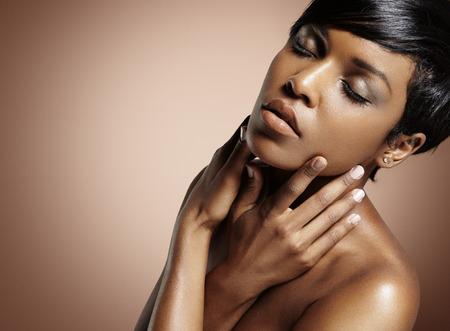 schwarze Frau mit geschlossenen Augen ihr Gesicht zu berühren Standard-Bild