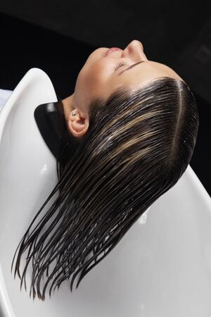 sylist: womens head in a shower in salon ready for a hair treatment