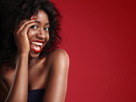 lachende zwarte vrouw op een rode achtergrond