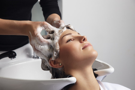 the caucasian beauty: hairdresser making a hair treatment in salon