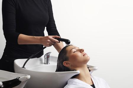 mooie jonge vrouw krijgt een haar gewassen door kapper bij salon