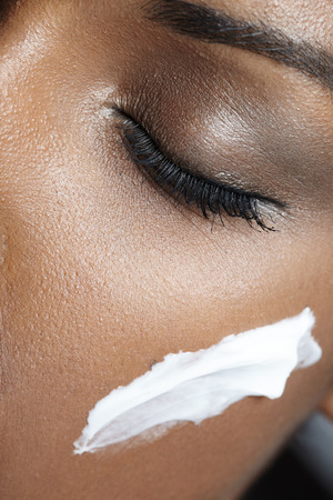 beauty eyes: black woman with closed eyes use a cream