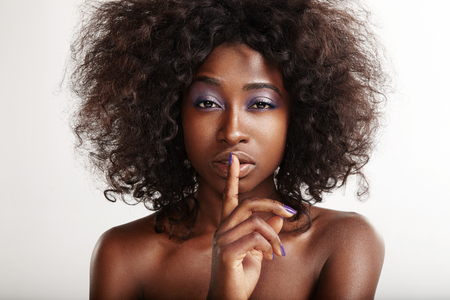 silently: pretty black woman with a finger on her lips making shhh! Stock Photo