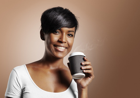 latin woman smiling and holding coffee on a warm beige background Stockfoto