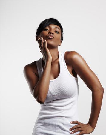 Donna di colore che trasmette un bacio che indossa bianco superiore Archivio Fotografico - 34638390