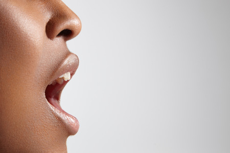 woman shouting: profile of a black woman with open mouth Stock Photo