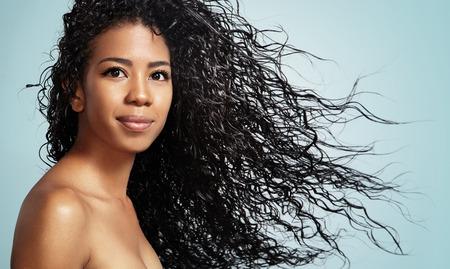 champu: mujer de negro con el pelo rizado que mira a la cámara