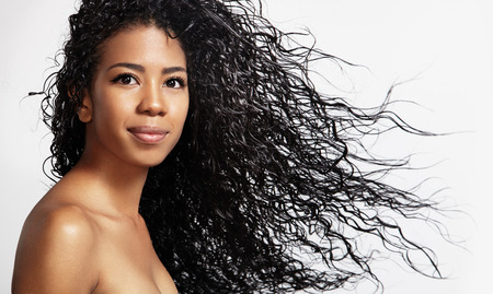 beauty black woman with curly blowing hair Stock Photo