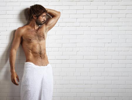 sauna nackt: Mann im Tuch und Backsteinmauer hinter
