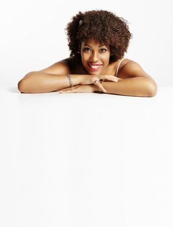テキストのためのスペースを持つテーブル上に横たわって幸せ黒人女性 写真素材