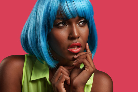 bright pportrait of a black woman wearing blue wig
