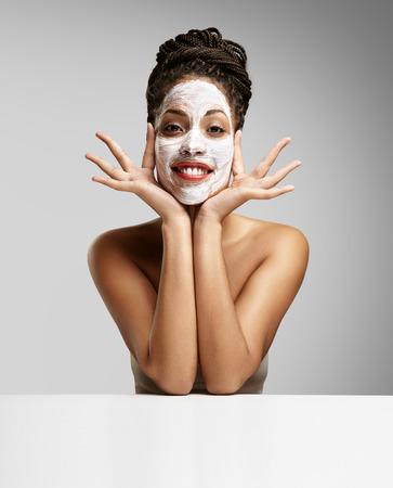 顔のマスクを持つ楽しい黒女性 写真素材