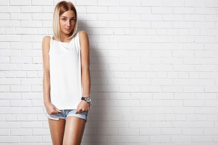 Donna che indossa t-shirt bianca contro muro di mattoni Archivio Fotografico - 34674786
