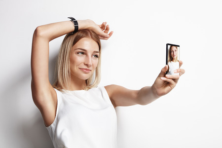 Meisje, het maken van een selfie op een witte muur Stockfoto - 34674787